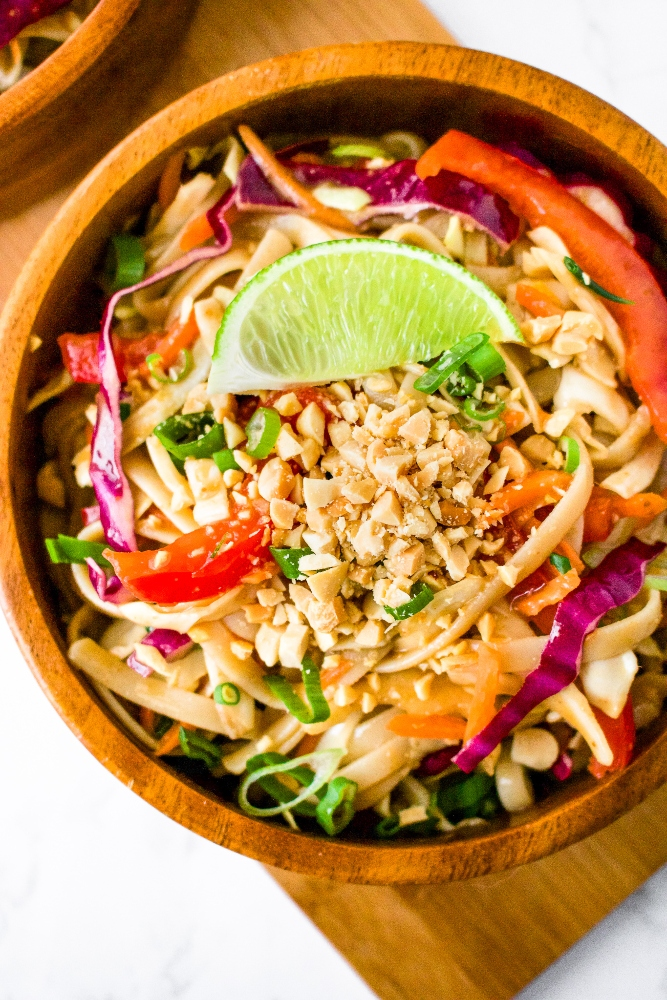 Close-up overhead shot of a cold peanut lime noodle salad in a bamboo bowl with colorful vegetables and a lime wedge / chopped peanuts on top.