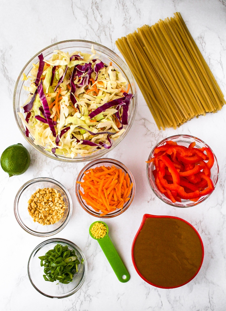 An overhead shot of the ingredients you need for cold peanut lime noodles: noodles, coleslaw mix, shredded carrots, sliced red peppers, scallions, ginger, peanut sauce or satay sauce, a lime, and chopped peanuts.