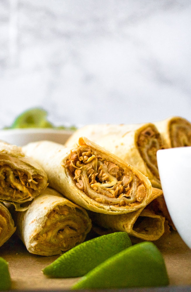 These crispy air fryer vegan taquitos are made with a meaty, flavorful jackfruit and refried beans filling with a quick dairy free queso sauce. This tasty vegetarian appetizer recipe is fun to make and is always a huge hit! Serve them with your favorite dips for a game day plant-based platter or for a cozy date night in. Or serve them with some rice and beans for a complete family dinner.