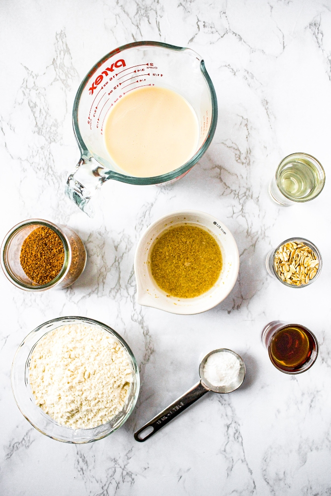 Overhead shot of the ingredients in vegan pancakes with coconut bacon: non-dairy milk, flax egg, baking powder, all-purpose flour, plant-based bacon, maple syrup, oats, and coconut oil.
