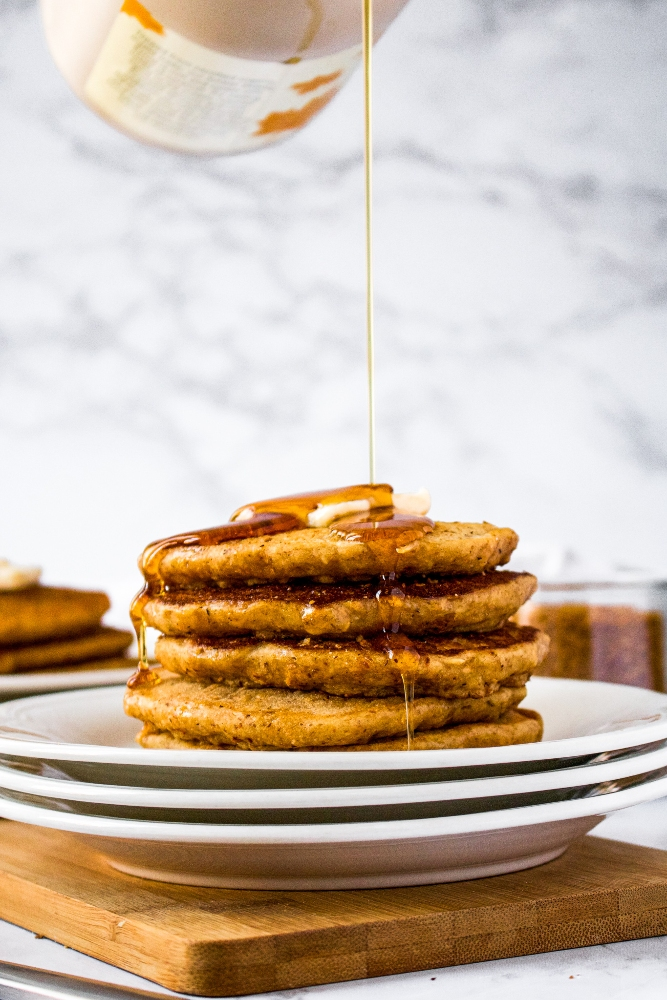 A stack of vegan pancakes with coconut bacon stacked on a small white plates topped with a square of vegan butter and a drizzle of maple syrup.