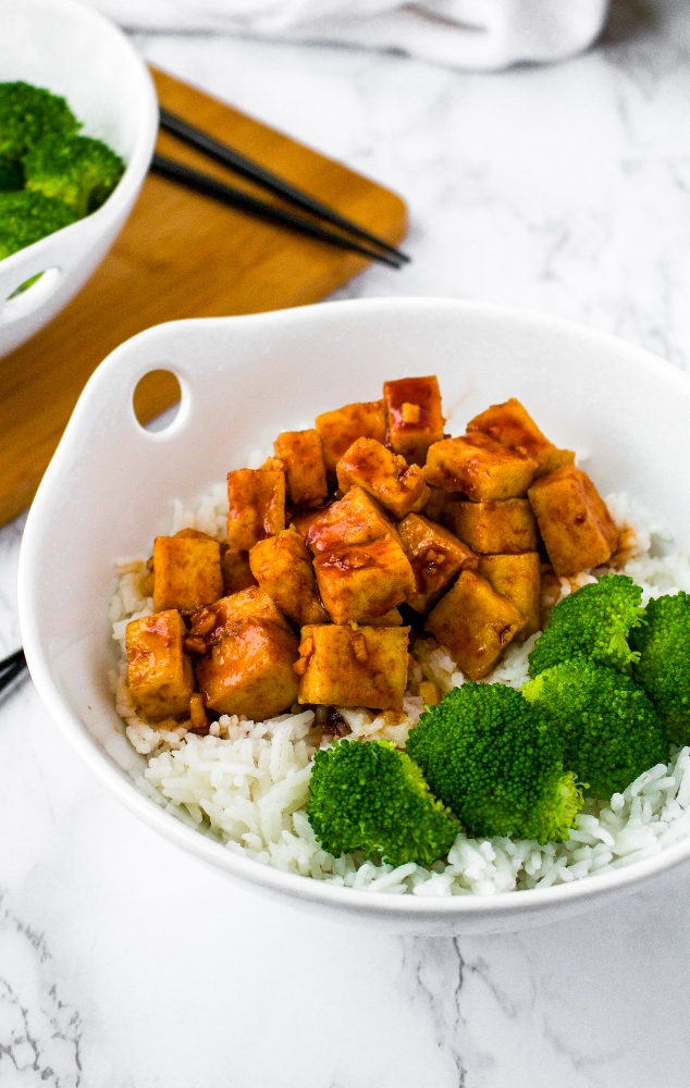 This easy air fryer tofu with a sweet sriracha sauce is our favorite quick tofu recipe! It's perfect for a healthy weeknight dinner or meal prep lunch. Tofu is diced and air fried (with no oil needed!) and then tossed in a sweet and spicy sriracha sauce. Serve this sweet sriracha tofu recipe over rice and roasted veggies or in a vegetable stir fry!