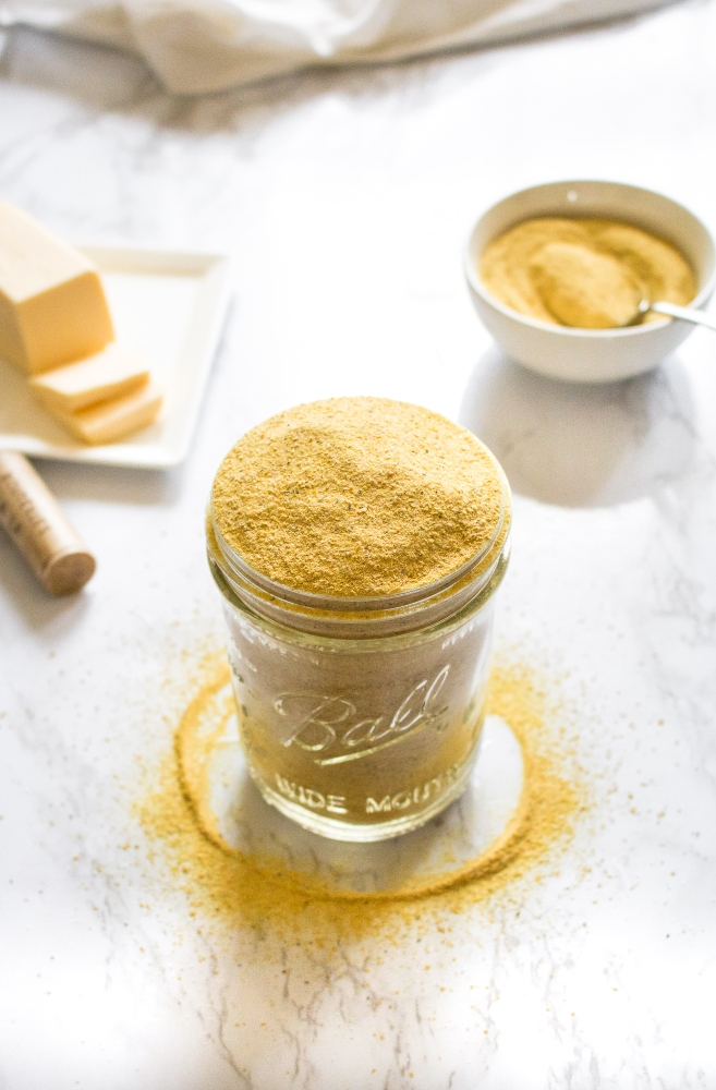 This easy 6-ingredient vegan cheese seasoning is a staple in our kitchen! Use it as a dairy-free parmesan on pasta, a cheesy popcorn seasoning, and mix it with vegan butter to make the BEST dairy-free garlic bread. It can also be used to make an easy cheesy pasta sauce! #vegan #vegancheese #veganseasoning #dairyfree #plantbased #nutritionalyeast #veganpopcorn