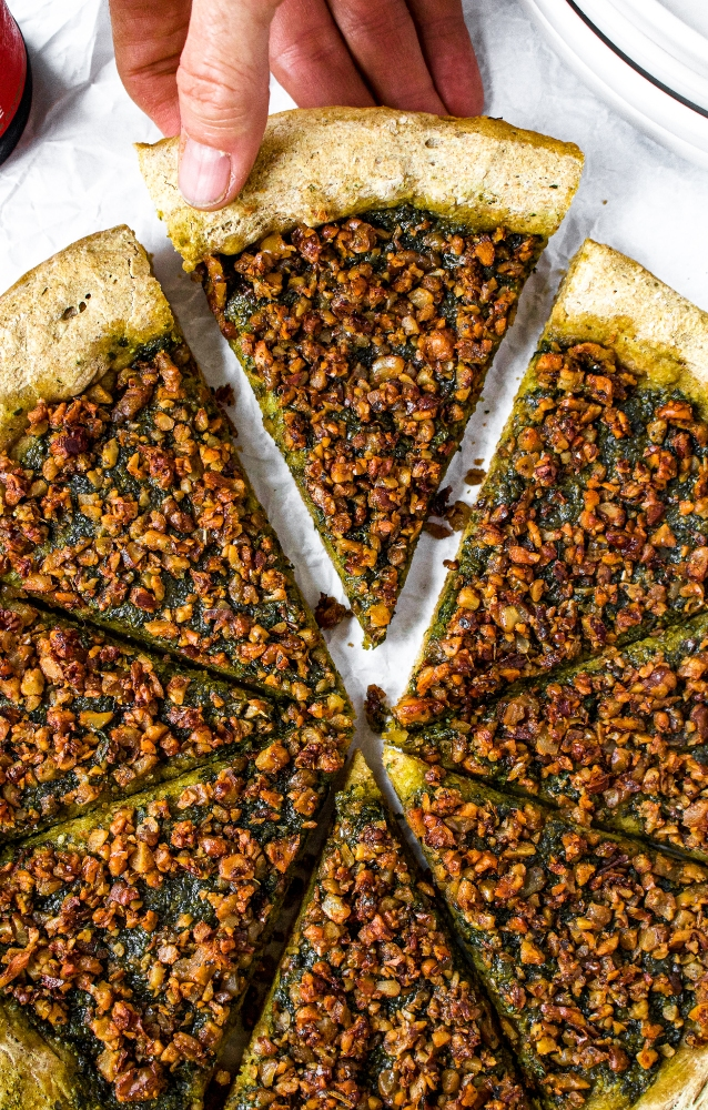 This quick no-proof vegan sausage and pesto pizza will prove itself with flavor time and again. Vegan pesto pizza is packed with dairy-free basil pesto sauce and wall-to-wall sausage-style walnut meat. The rustic whole wheat vegan pizza dough is easy to make, self-rising, and beer-based (which gives the crust its rich flavor). This healthy vegetarian pizza recipe can be made in under 40 minutes - less than the time it would take a yeasted dough to rise in its first proof!