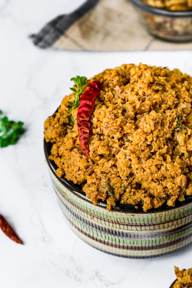 A close-up photo of vegan walnut taco meat in a green and brown striped bowl. There is a single dried red chili on top along with a sprig of oregano. A ramekin of raw walnuts is in the background.