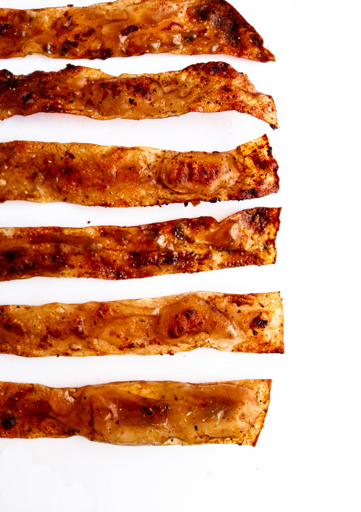 This rice paper bacon is so easy and fun to make! It requires simple pantry ingredients you can keep on hand for whenever that smoky-salty-sweet craving strikes. It can easily be made gluten-free and tastes shockingly like the bacon we grew up eating! #vegan #bacon #veganrecipes // plantpowercouple.com
