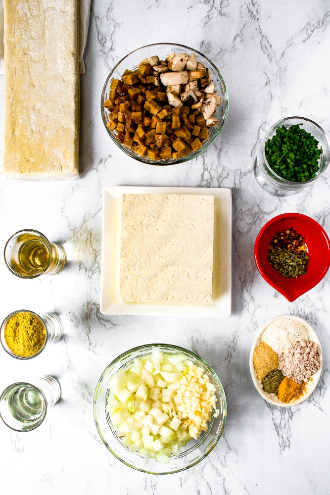 Ingredients you need to make a vegan quiche: firm tofu, onions, garlic, refined coconut oil, nutritional yeast, rice vinegar, chives, vegan ham, mushrooms, dairy-free puff pastry, and spices.