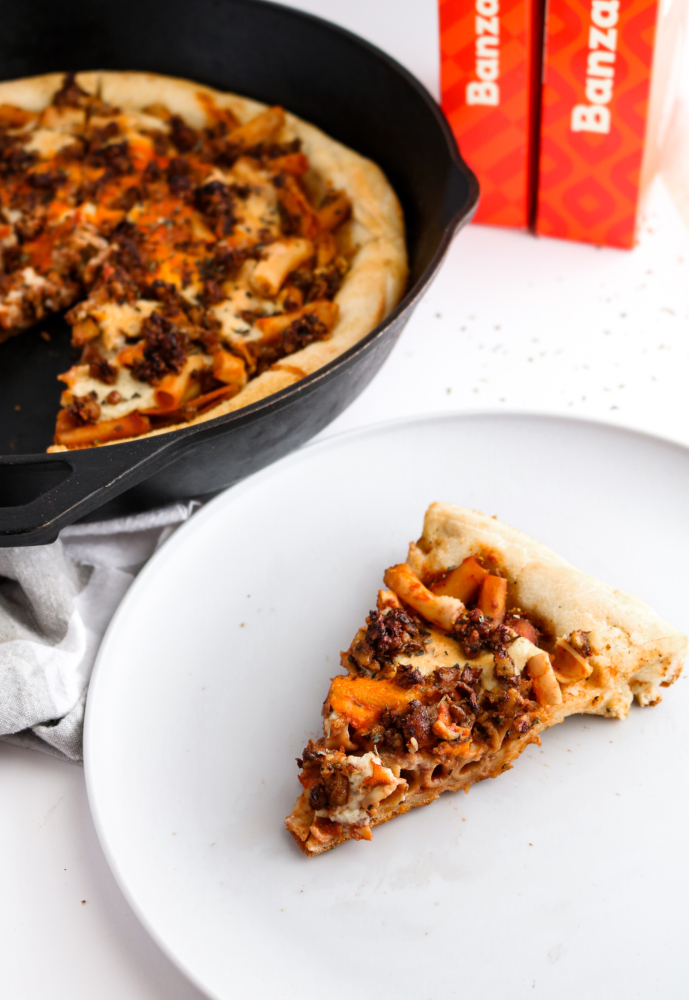 This Vegan Baked Ziti Pizza is like a delicious dream: Saucy chickpea ziti, flavorful walnut sausage, and an ooey gooey mozzarella sauce on a fluffy pizza crust baked to perfection in your cast iron pan. #vegan #vegetarian #pizza #ziti #walnuts // plantpowercouple