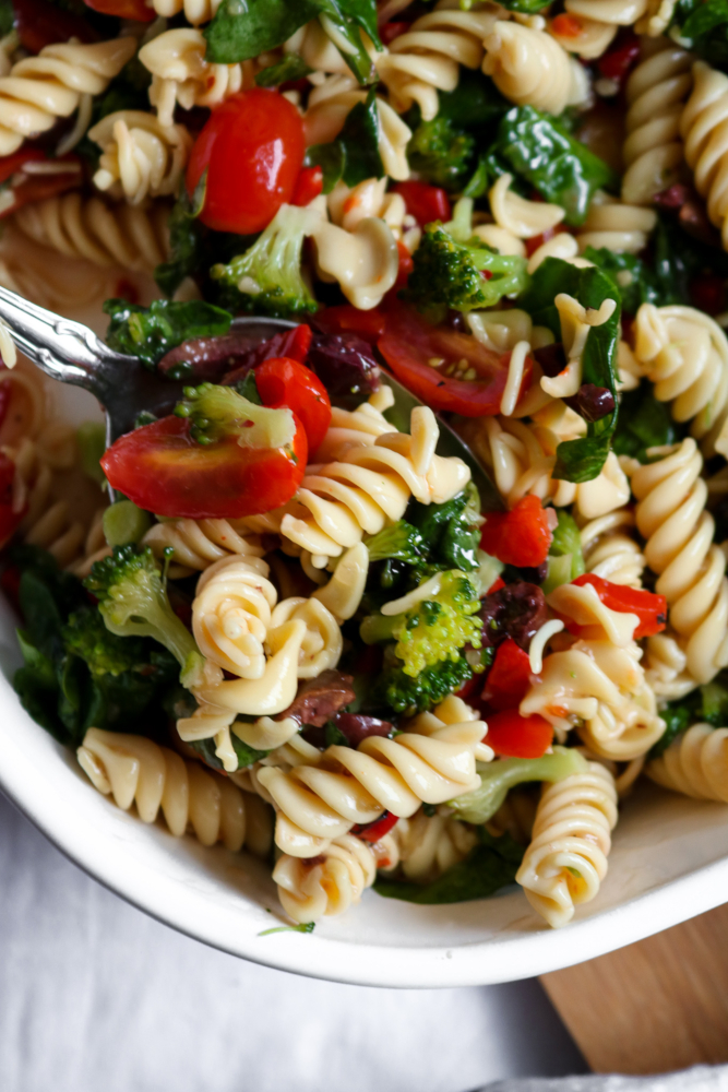 "This simple vegan pasta salad recipe is a ""grown-up-riff"" off the traditional side dish my Gram used to make for me at ALL the family BBQs + parties. It's quick, easy to make and bursting with flavors of fresh veggies like red peppers, tomatoes, kalamata olives, and more! #vegan #plantbased #recipe #summer #sidedish // plantpowercouple.com"