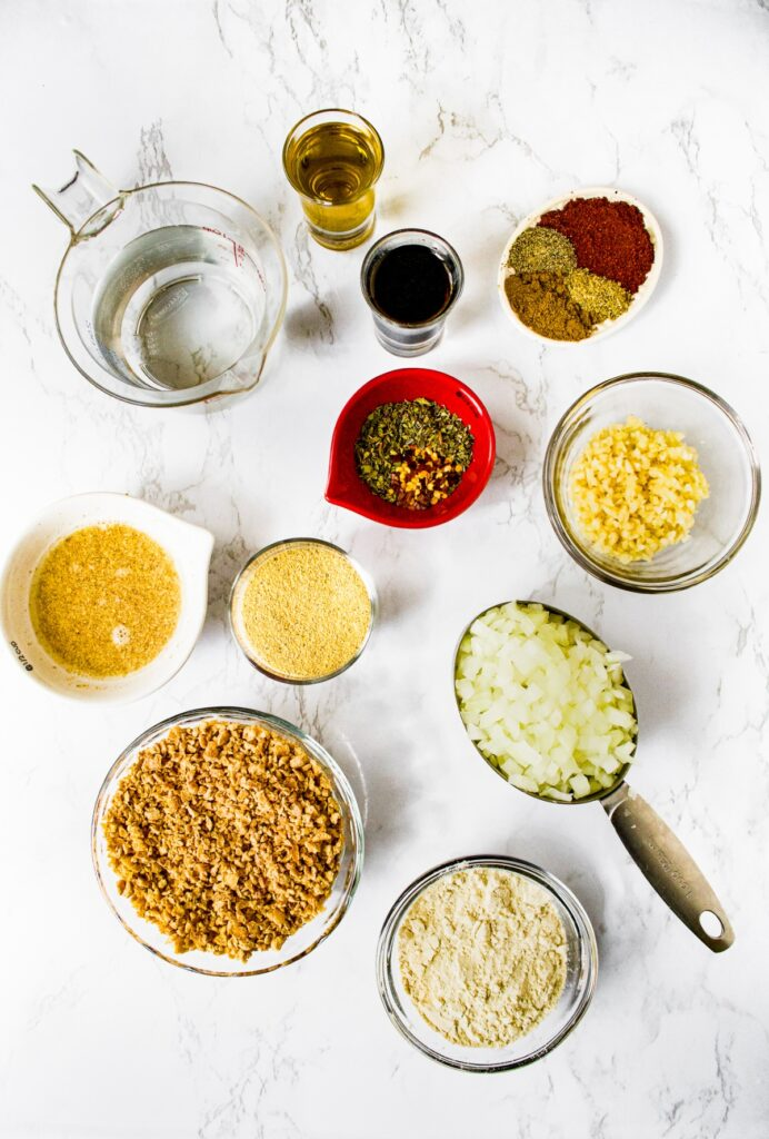 An overhead shot of all the ingredients you need to make the best homemade vegan meatballs: TVP, onion, vital wheat gluten, flaxseed egg, nutritional yeast, garlic, water, olive oil, soy sauce, Italian seasoning, chili powder, crushed red pepper flakes, pepper, onion powder, and ground cumin