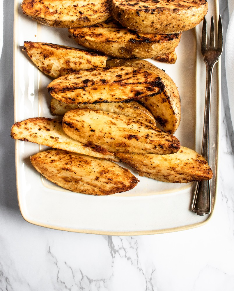 These cast iron potato wedges recipe is easy to make, super dependable, and can be altered to your specific spice/flavor desires. A healthier alternative to french fries, they're great paired with ALL your summer grilling favorites or just as a snack served with ALL the dips! #vegan #potatoes #potatowedges #plantbased #castiron #comfortfood #veganrecipe