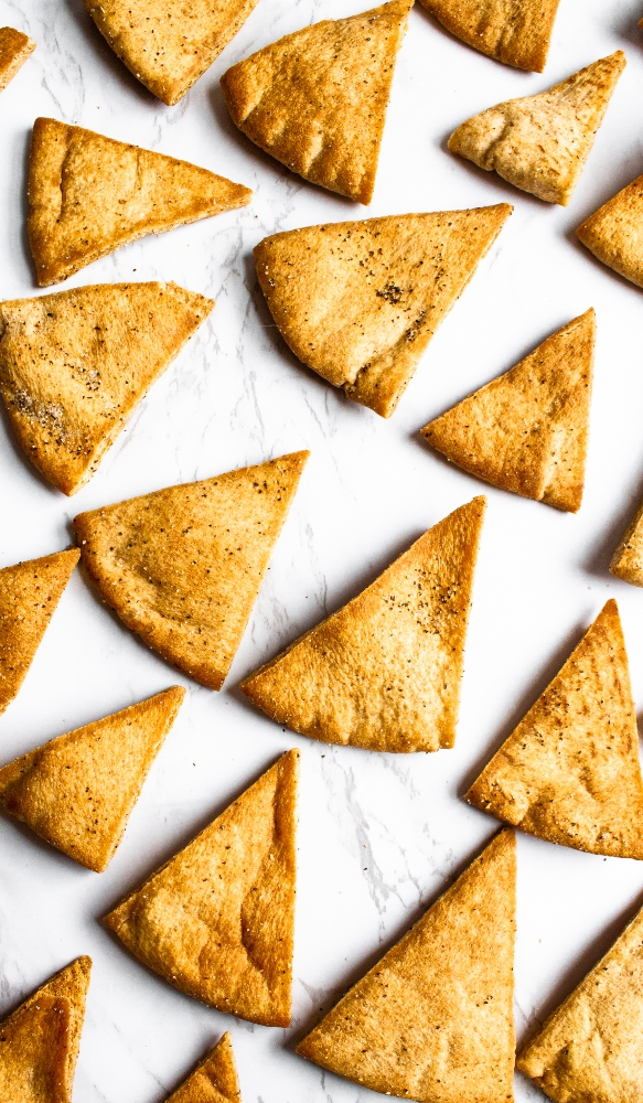 Make your own pita chips in the air fryer with just 4 ingredients and 20 minutes of your time! Perfect for snacking or dipping in hummus. #vegan #veganrecipe #airfryer #airfryerrecipes #pitachips #easyveganrecipes #vegansnack #homemade