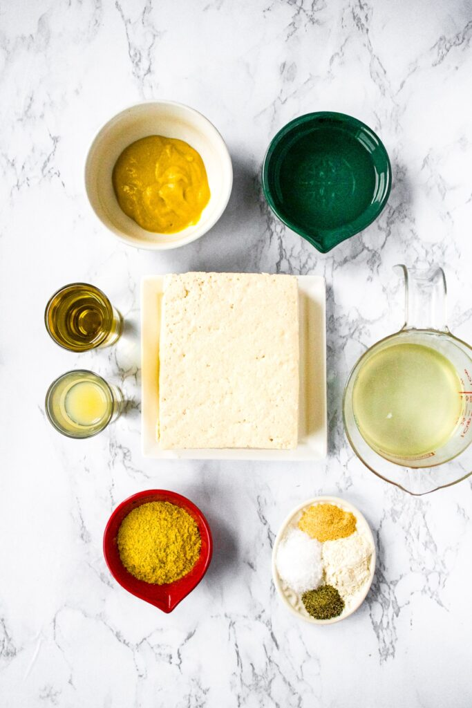 Overhead shot of all the ingredients needed to make a vegan cheese ball: extra firm tofu, yellow mustard, lemon juice, nutritional yeast, sea salt, onion powder, pepper, refined coconut oil, olive oil, and water.