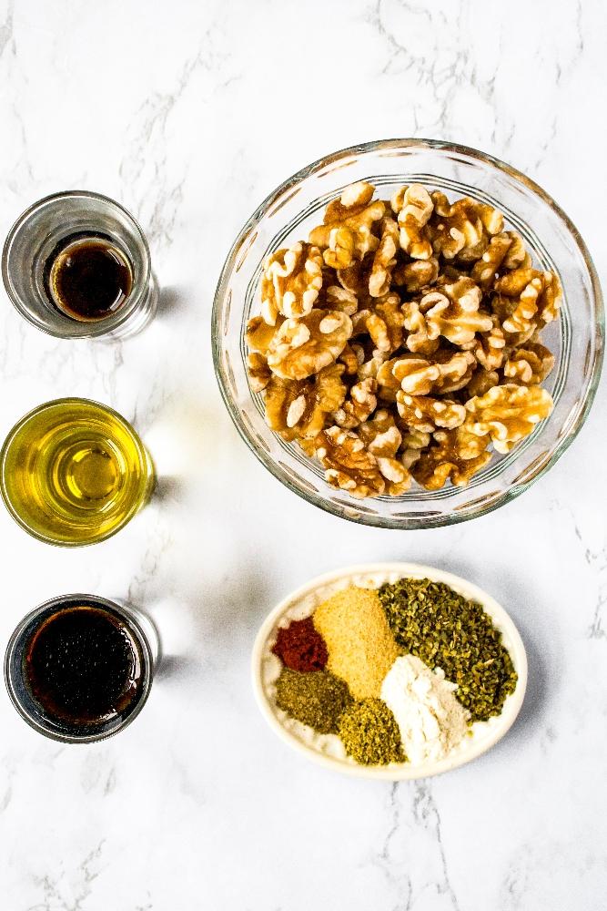 Overhead photo of the ingredients in walnut sausage: soaked walnuts, olive oil, liquid smoke, soy sauce, garlic powder, onion powder, ground fennel, smoked paprika, and celery salt.