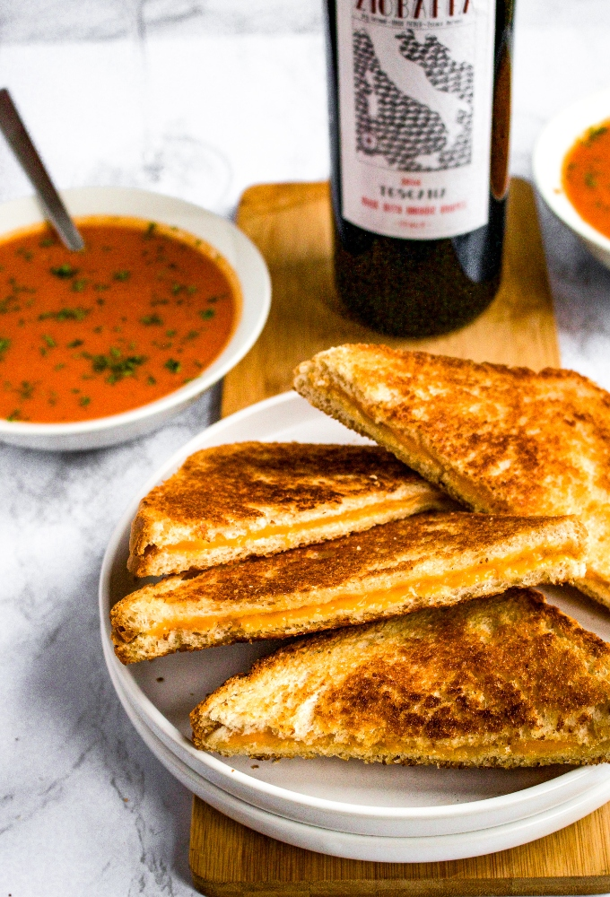A plate with a pile of vegan grilled cheese sandwiches cut in half to make triangles. There is a bowl of dairy-free cream of tomato soup and a bottle of sangiovese in the background.