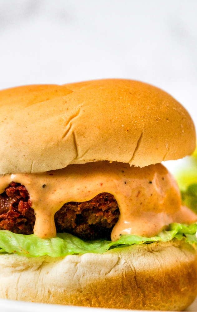 Easy vegan burger sauce sliding down the side of a plant-based hoemmade burger on a bun with a lettuce leaf.