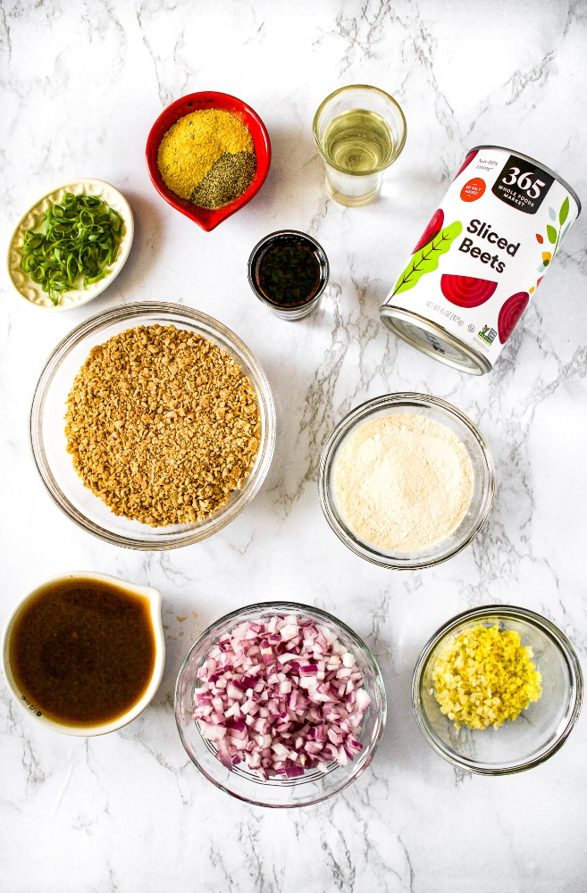 Ingredients needed to make vegan teriyaki burgers: teriyaki sauce, minced red onion, minced garlic, minced ginger, refined coconut oil, a can of beets, TVP, bouillon powder, ground black pepper, scallions, soy sauce, and vital wheat gluten.