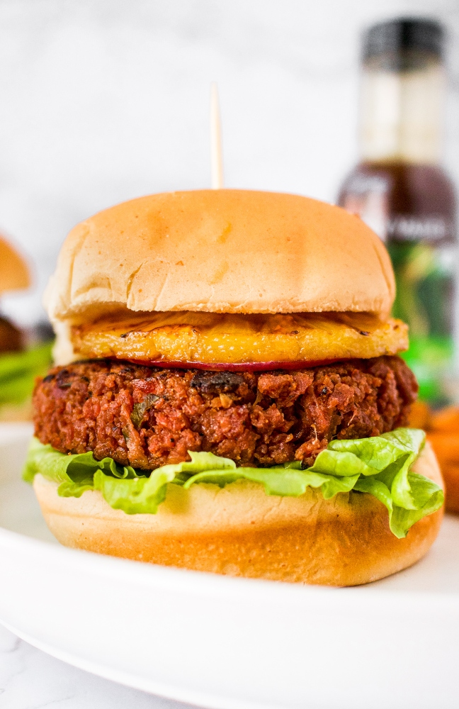 This Hawaiian-inspired vegan teriyaki burger is the meatiest and tastiest on the planet! If you love teriyaki chicken, you're going to love this plant-based homemade burger! It starts with a blend of TVP and vital wheat gluten with a little beet puree thrown in for a meaty color. Then, it's flavored with the perfect blend of garlic, ginger, red onion, and teriyaki sauce. It's topped with a grilled pineapple slice and spicy teriyaki mayo. It's a great vegetarian option for cookouts and guaranteed to be your new favorite summer veggie burger.