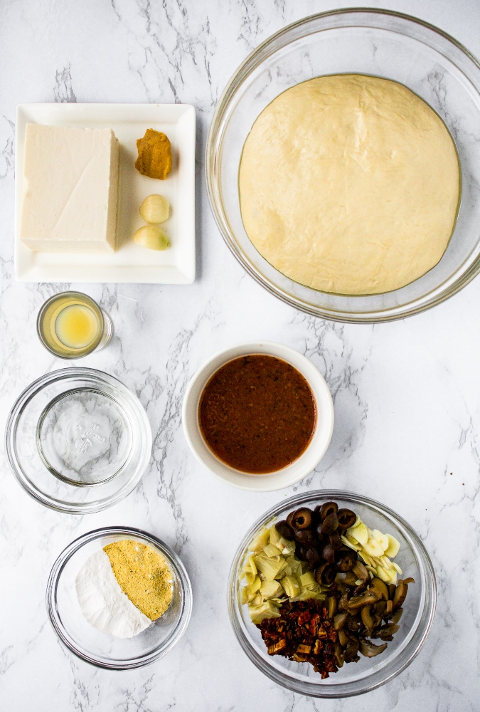 Vegan white pizza ingredients: pizza dough, silken tofu, miso paste, fresh garlic, lemon juice, refined coconut oil, tapioca starch, vegan cheese seasoning, sun-dried tomato vinaigrette, mushrooms, olives, artichokes, sun-dried tomatoes, and sliced garlic.