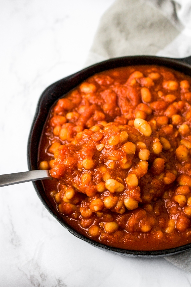 Vegan baked beans in a cast iron skillet with a spoon lifting some out. This delicious, healthy take on classic baked beans is filled with flavor but uses simple ingredients (and no ketchup!) on the stove.