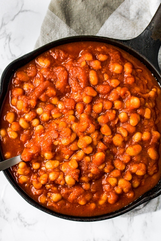 Overhead close up of vegan baked beans in a small cast iron skillet with a black and white checkered napkin. Stovetop beans are so easy to make, you'll be eating them all summer long alongside ALL your cookout favorites! The process is super basic, not to mention oil-free AND done in about half an hour!