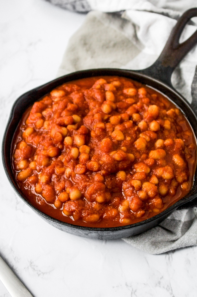 A skillet of healthy vegan baked beans with a black and white checkered napkin on a grey marble background. These easy vegan baked beans are the perfect summer BBQ side dish!
