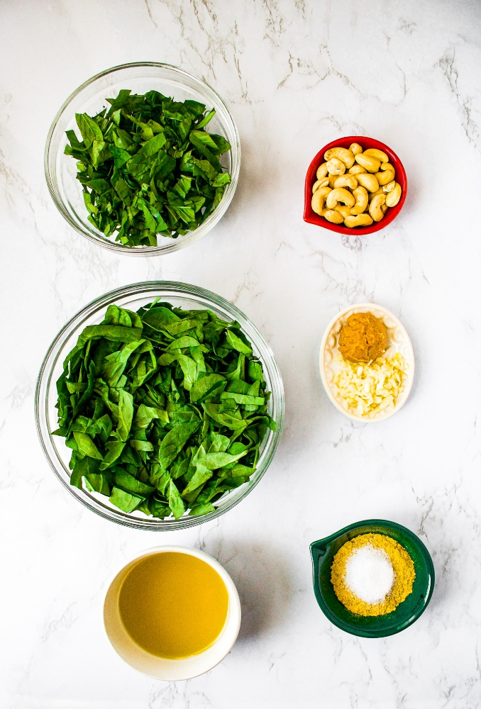 Vegan pesto ingredient shot: shredded spinach, shredded fresh basil, olive oil, raw cashews, white miso paste, minced garlic, nutritional yeast, and sea salt.