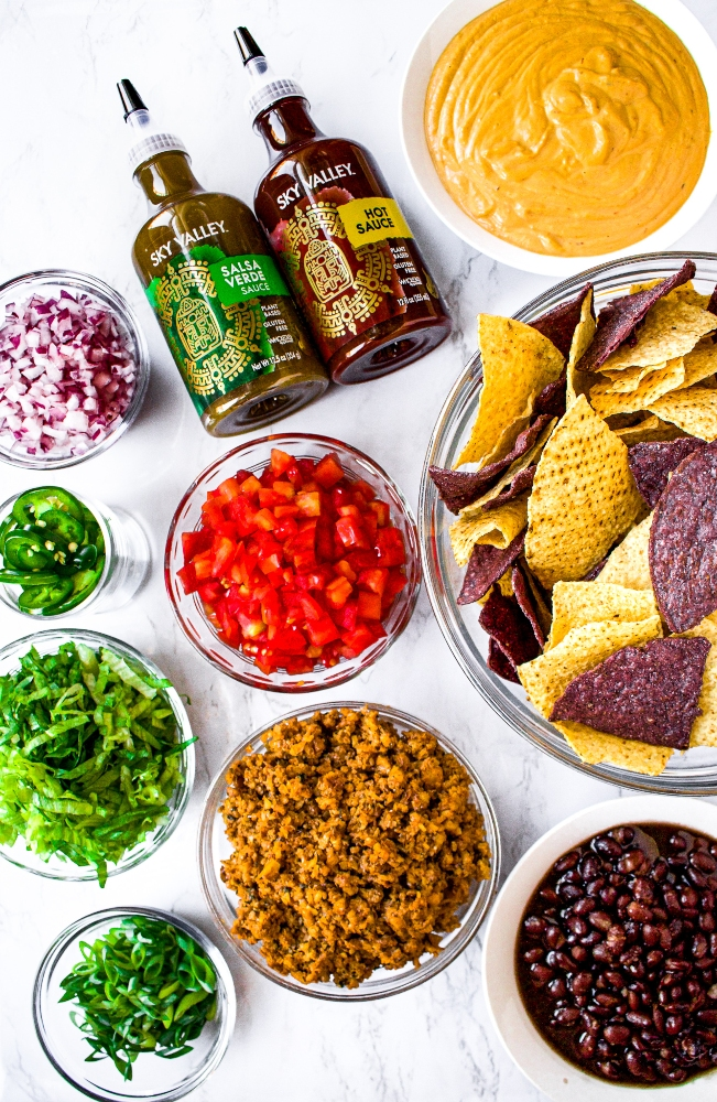 An overhead shot of the ingredients in dairy free and vegetarian loaded nachos - walnut meat, black beans, scallions, shredded lettuce, jalapenos, diced tomatoes and red onion, salsa verde and hot sauce, dairy free nacho cheese sauce, and chips.