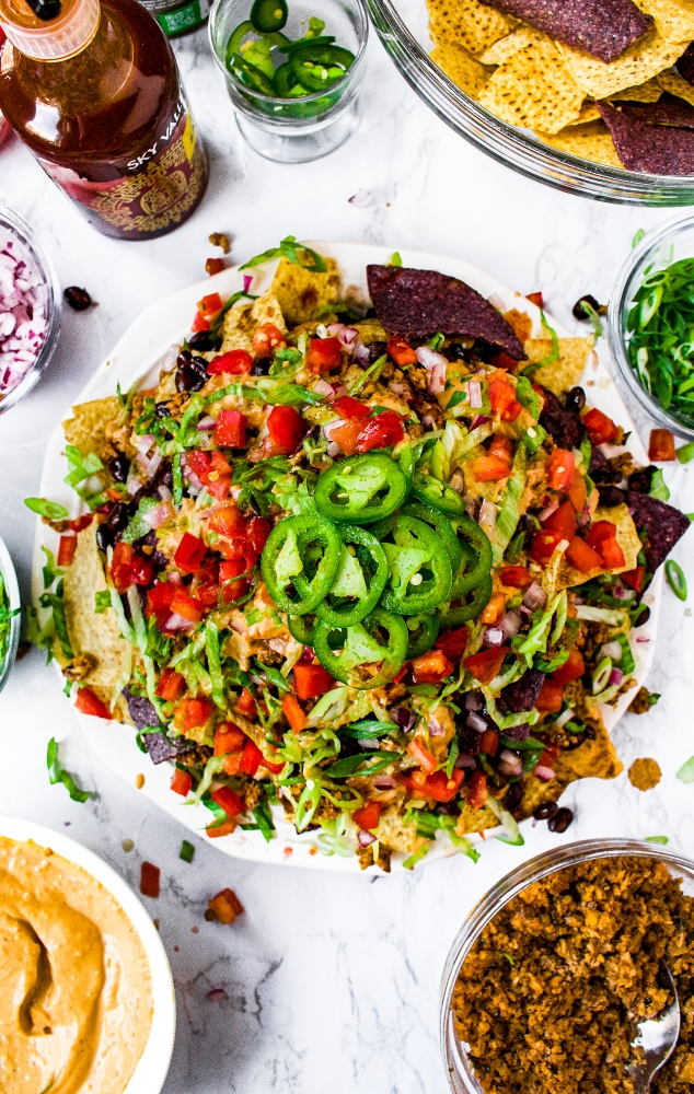 An overhead shot of a large plate of vegan nachos, piled high with walnut meat, dairy free nacho cheese sauce, and vegetables. Topped with sliced jalapenos and surrounded by extra plant-based nacho toppings.
