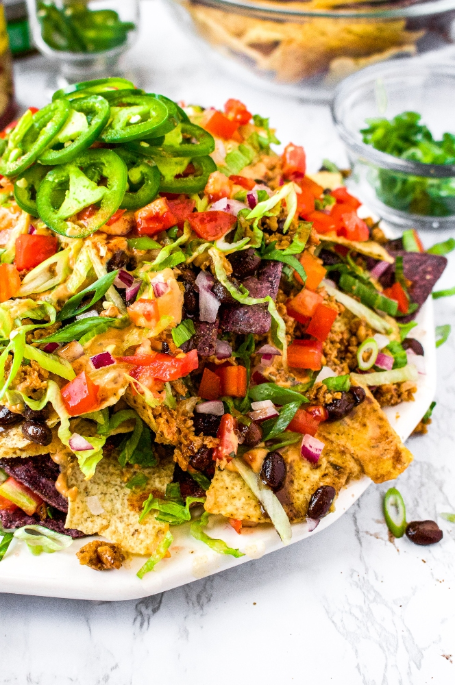 A close-up shot of a large plate of vegan nachos, piled high with walnut meat, dairy free nacho cheese sauce, and vegetables. Topped with sliced jalapenos.