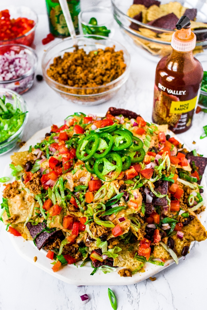 A photo of a big pile of vegan nachos on a white plate piled with spicy beef-style walnut meat, dairy free nacho cheese sauce, diced tomatoes and red onion, shredded lettuce, and sliced jalapenos. Extra toppings in clear bowls can be seen in the background.